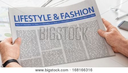 Man Reading Newspaper With The Headline Lifestyle And Fashion