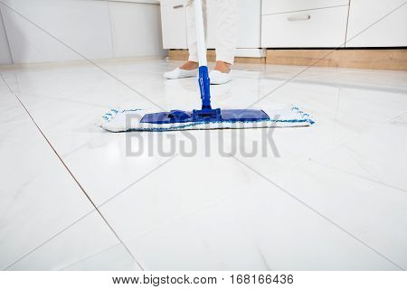 Cleaning Service Woman Mopping The Floor In Kitchen Inside House