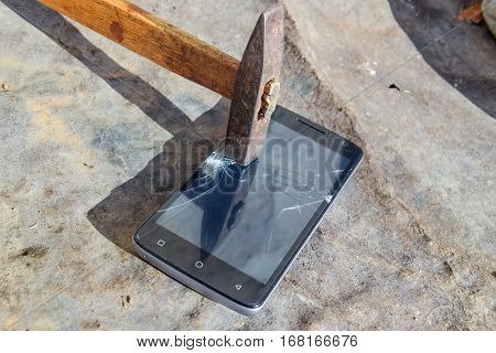 Hammer And Smartphone. The Screen Of The Smartphone, A Broken Ha
