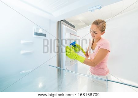 Cleaning Service Professional Woman Cleaning Inside The Refrigerator With Spray Bottle And Sponge