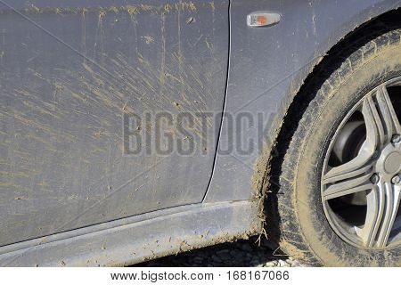 The mud on the wheels fenders and car doors. The result is a trip through the mud. Dirty car.
