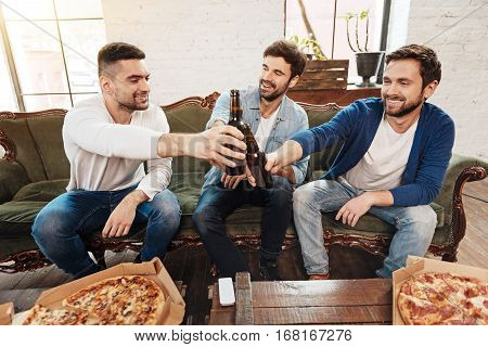 Cheers my friends. Positive joyful nice men sitting on the sofa and holding beer bottles while cheering with them