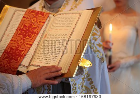 male hand of holy church priest with paper bible or book with open pages and cross on fabric closeup