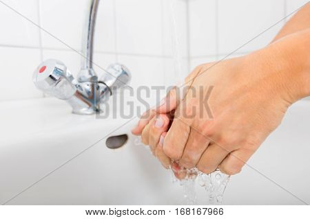 Close-up Of Woman Washing Hands In The Basin After Cleaning The Room