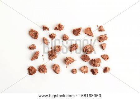 Milk chocolate morsels on white background