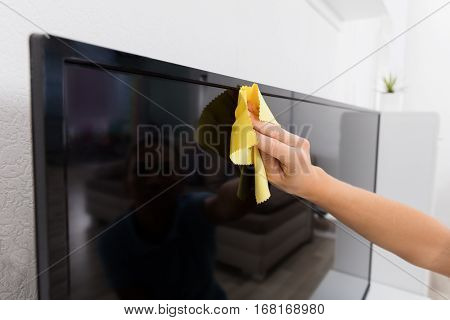 Close-up Of Woman Using Cloth To Clean The Television At Home