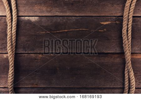 weathered ship ropes on old wooden plank background
