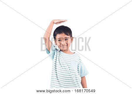cute boy measures his height with his hand on the head