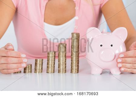 Close-up Of Woman Hands Protecting Piggybank With Stack Of Coins At Desk