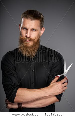 Serious hipster man with beard and mustashes holding scissors, over grey background