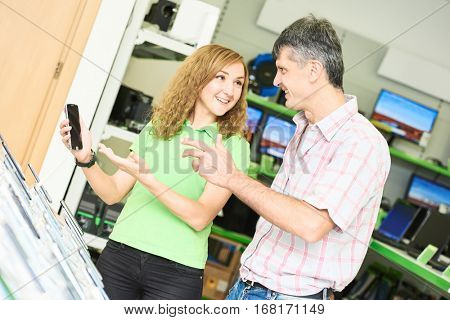 Seller assistant woman help purchaser choosing mobile phone