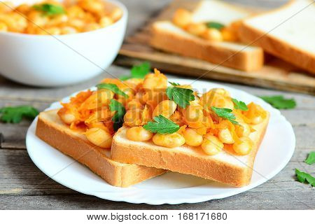 Baked white beans on toast. Beans baked with carrots, garlic and tomato sauce and garnished with fresh parsley. Homemade vegetarian white beans recipe. Closeup