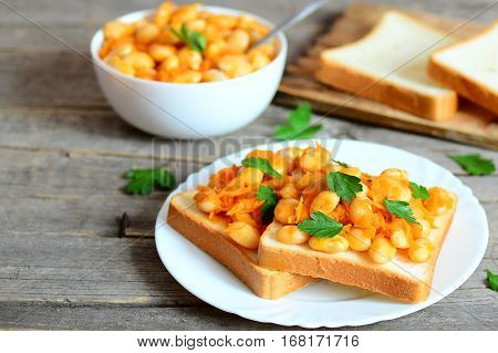 Baked white beans with vegetables on bread and on plate. Baked white beans in a bowl, bread slices on wooden background with copy space for text. Healthy vegetarian food