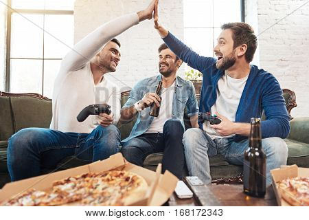 Draw game. Positive happy male friends holding game consoles and giving high five while ending a game in a draw
