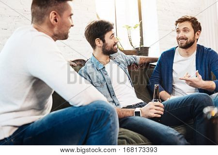 Pleasant communication. Cheerful nice bearded man gesticulating and smiling while telling his friends a story