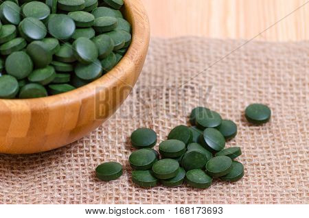 green pills spirulina and chlorella seaweed close up on the wooden background