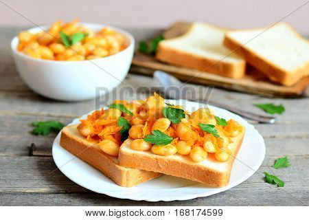 Open sandwiches with baked white beans. Beans baked with carrots, garlic and tomato sauce on a bowl, bread slices, spoon, fresh parsley on a rustic wooden table. Vegetarian and vegan protein dish