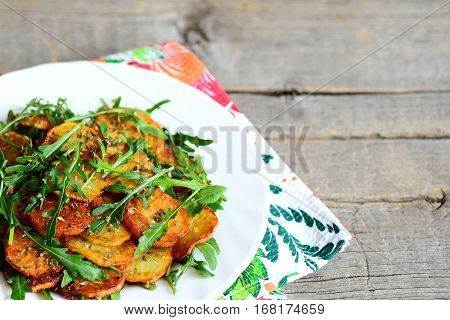 Spicy potatoes with arugula on a white plate and wooden background with empty place for text. Pan fried potatoes with fresh arugula and dry spices. Fast and savory vegetable side dish. Closeup