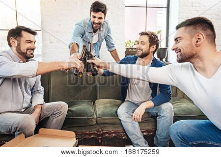 Saying a toast. Joyful positive happy men sitting together and clinking bottles of beer while saying a toast