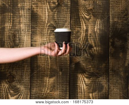 Paper Or Plastic Coffee Cup In Hand On Wooden Background