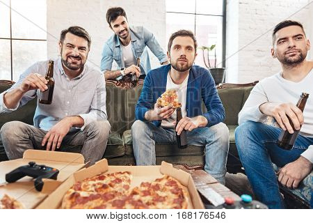 Meeting with friends. Serious concentrated bearded man holding a slice of pizza and watching a football match while spending time with his friends