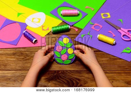 Child holds a felt Easter egg decor in his hands. Child made simple Easter crafts. Sewing tools and materials on a wooden table. Creating a pattern on felt Easter eggs