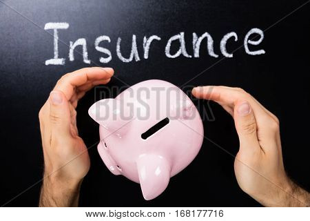 Close-up Of Person Hand Protecting Piggybank Showing Insurance Concept On Blackboard