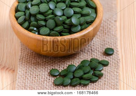 green pills spirulina and chlorella seaweed close up on the wooden