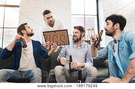 Piece o art. Nice pleasant delighted man standing behind the sofa looking at the picture while enjoying time with his friends