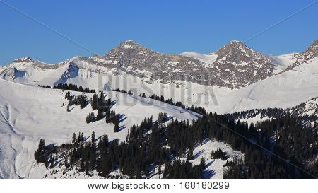 Snow covered mountain range in the Swiss Alps. Mount Vanil Noir and other peaks seen from the Rellerli ski area.