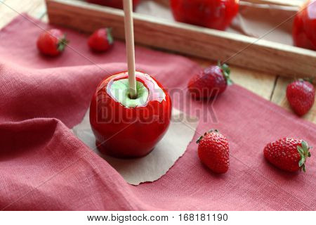 Candy apple with strawberry on pink fabric closeup