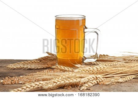 Glass of beer and spikes on wooden table and white background