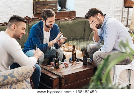 Playing card games. Happy joyful positive man holding a pack of cards and laughing while playing card games with his friends