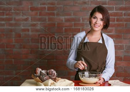 Young woman making dough for cakes on brick wall background