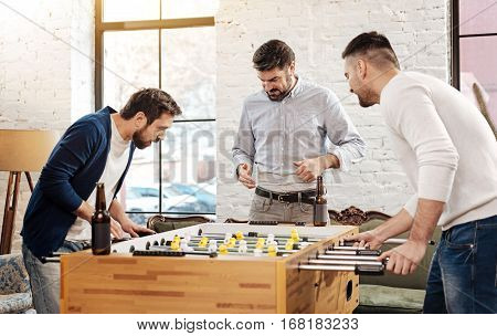 Table games. Handsome cheerful delighted men playing table soccer and focusing on the game while having fun together