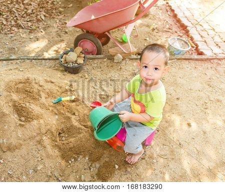 Thai Baby Boy Palying On  Pile Of Sand With Toy And Plastic Fork, Spoon , Truck
