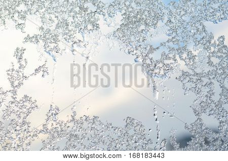 Icing on window glass frost on blue sky background in winter