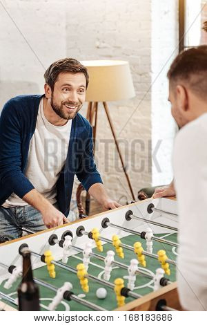 Close to victory. Cheerful joyful bearded man looking at his opponent and smiling while playing the table football with him