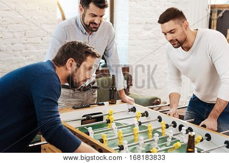 Football referee. Delighted smiling bearded man standing near the playing table and watching the game of his friends while being a referee