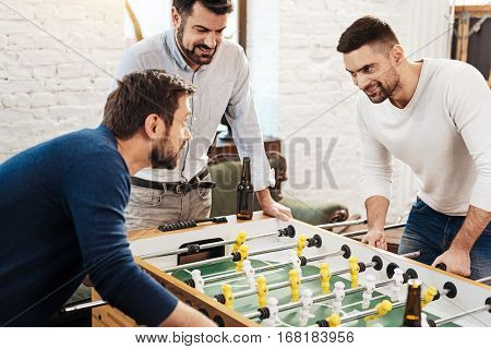 I will win. Handsome determined brutal man standing opposite his opponent and looking at him while intending to win the game