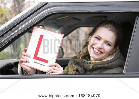 Young woman holding learner driver sign while looking out of car window