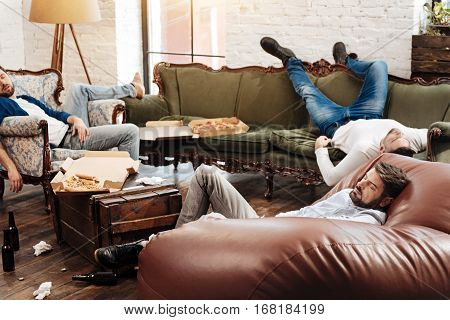 Absolute mess. Tired bearded young man lying on the sofa and sleeping while resting after a bachelors party