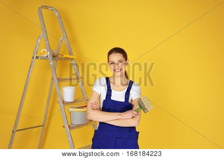 Beautiful young decorator on color background