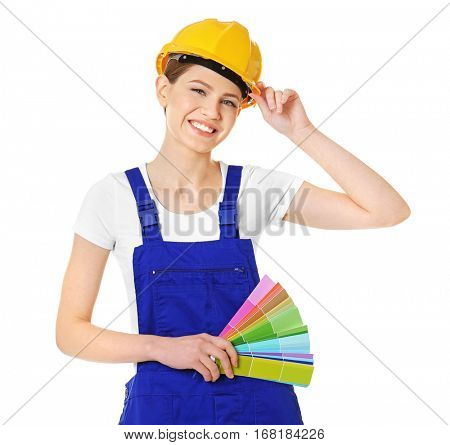 Beautiful young decorator with color samples on white background