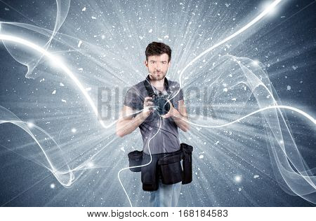 A young amateur photographer with professional photographic equipment taking picture in front of blue wall with dynamic white lines illustration concept