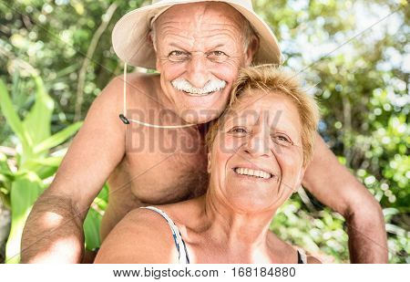 Senior happy couple having fun taking selfie at Thailand jungle trip on island hopping tour - Active elderly and travel concept around the world - Warm filtered look with focus on mature woman smile