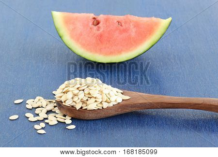 Watermelon seeds, which are dried and with their outer skin removed, in a wooden spoon, and in the background is a slice of fresh, organic watermelon fruit.