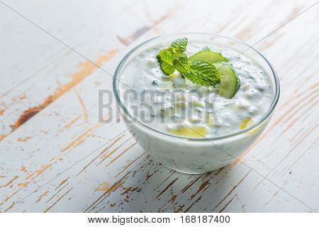 Tzatziki sauce and ingredients on rustic background