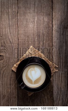 cup of cappuccino coffee on the old vintage wooden table