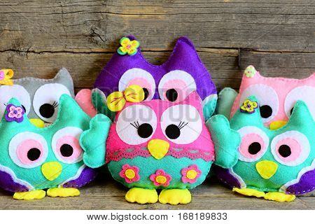 Nice kids felt toys. Colored stuffed owls toys on vintage wooden background. Decorations crafts made of felt. Fun kids background. Closeup